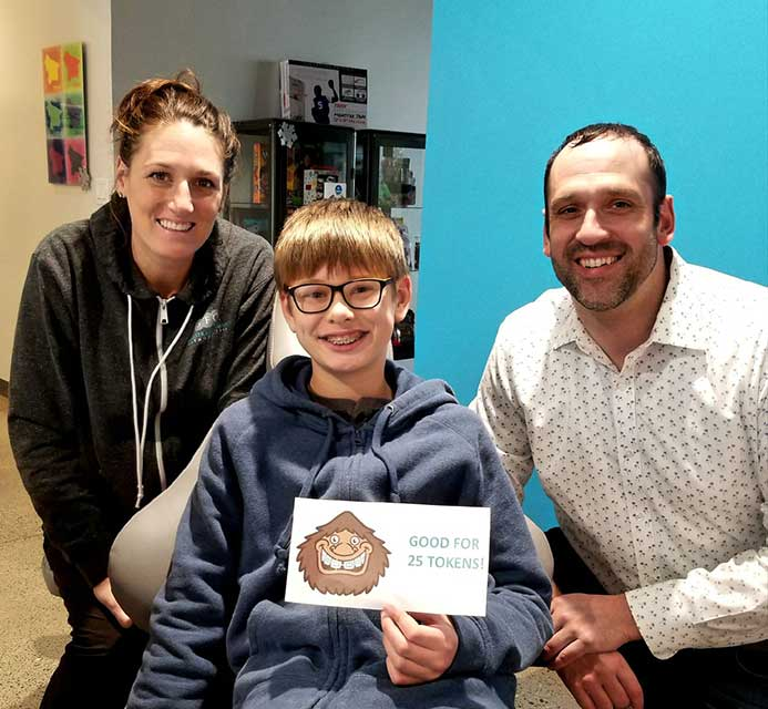 A contest winner posing with Dr. Seth Senestraro at Senestraro Family Orthodontics