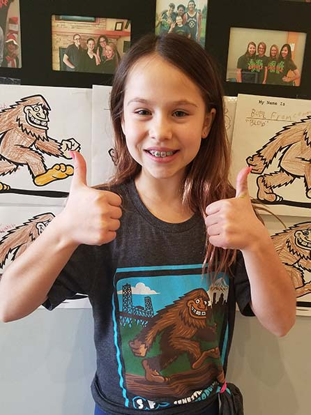 A girl doing thumbs up while wearing Sasquatch shirt at Senestraro Family Orthodontics