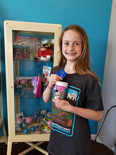 A girl holding token and her prize in the store at Senestraro Family Orthodontics