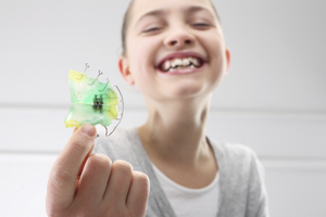 A young smiling girl holding a retainer at Senestraro Family Orthodontics.